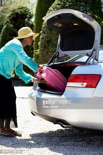 Woman loading suitcase into trunk of car, side view