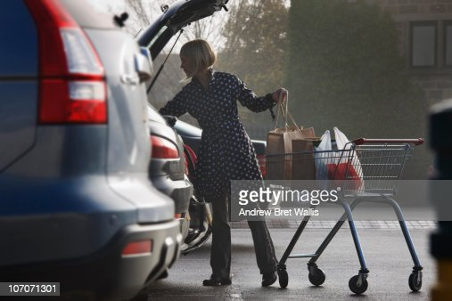 woman loading supermarket shopping into a car