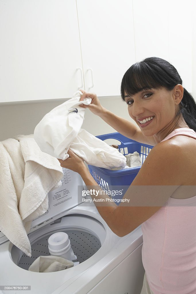 Woman loading washing machine, smiling, portrait