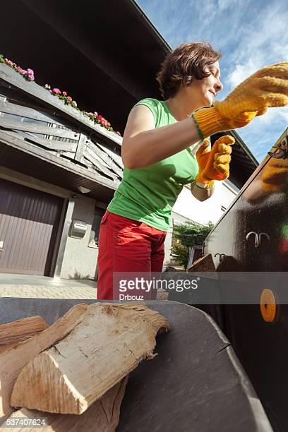 Femme de chargement de brouette de bois à brûler