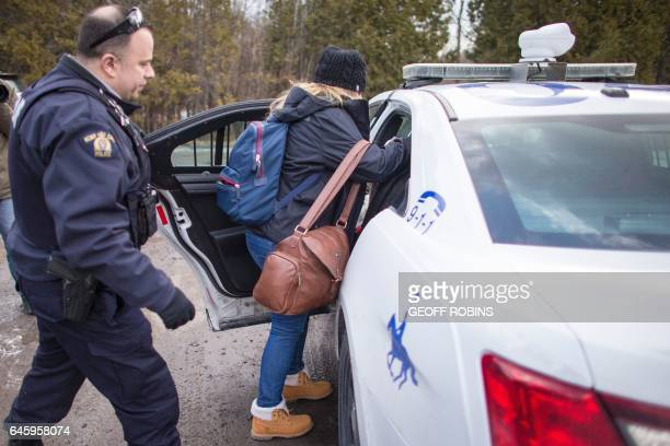A woman loads her baby into a RCMP cruiser after she and her husband were detained crossing the CanadaUS border near Hemmingford Quebecon February 27...