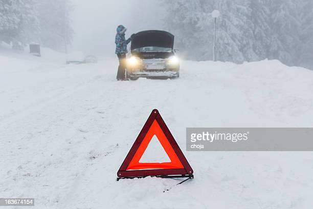 Frau loking in ihrer defekten Auto im Schnee blizzard.warning triangle