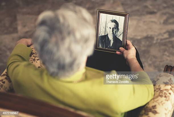 Woman look at a photo of a senior woman