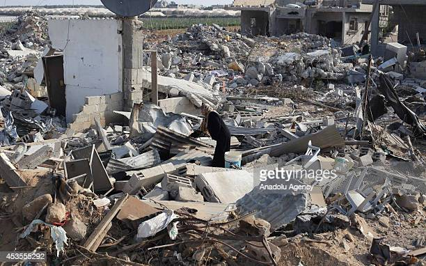 A woman look for usable belongings among the ruins of Fehari area of Khan Yunis as Palestinians try to survive in poor conditions in rambling tents...
