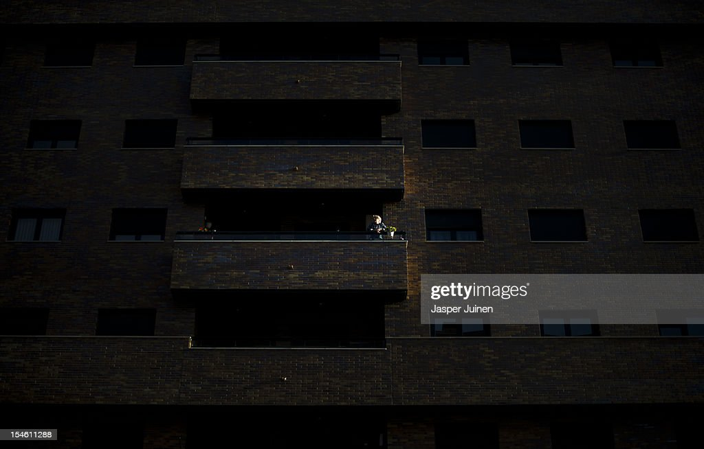A woman look on from her balcony on October 22, 2012 in Sesena, Spain. With a housing backlog of more than 1.2 million unsold newly build homes, banks in Spain have recenlty started to sell their real estate assets with discounts, some upto 80 percent, slashing prices to a level not seen for over 20 years. With morgages of 100 percent, some experts worry that mistakes from the past are repeated again.