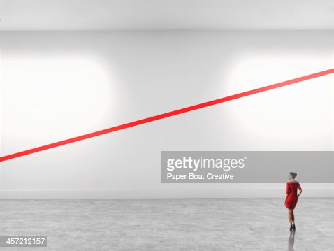 Woman looking at a diagonal red line in gallery