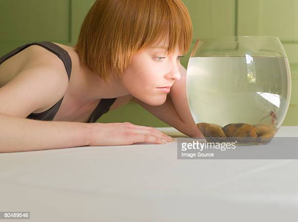 A woman looking at a goldfish bowl