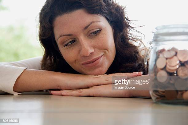 Woman looking at a jar of pennies