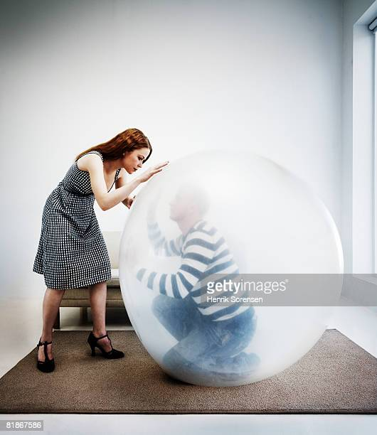 Woman looking at a man inside a balloon