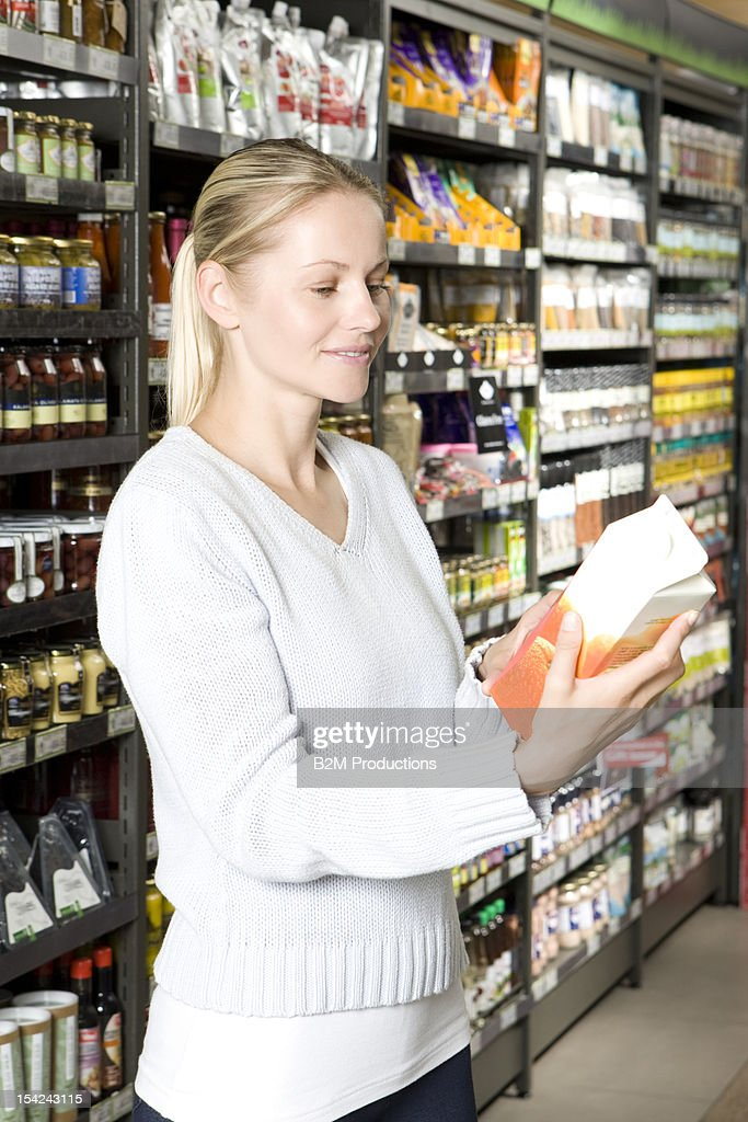 Woman looking at a milk carton in a supermarket : Stock Photo