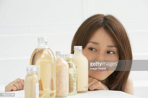 Woman looking at a row of cosmetics bottles