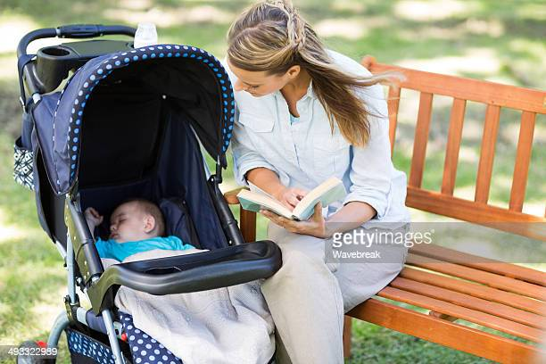 Woman looking at baby sleeping in carriage