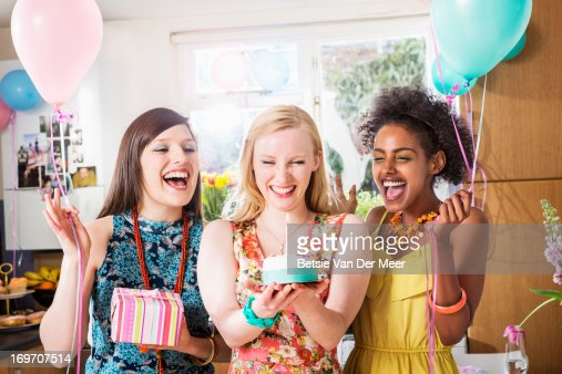 Woman looking at birthday cake, friends cheering. : Stock Photo