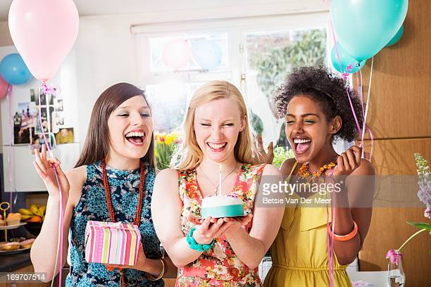 Woman looking at birthday cake, friends cheering.