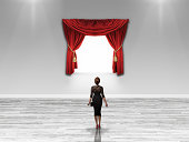 Woman looking at blank canvas with velvet curtains