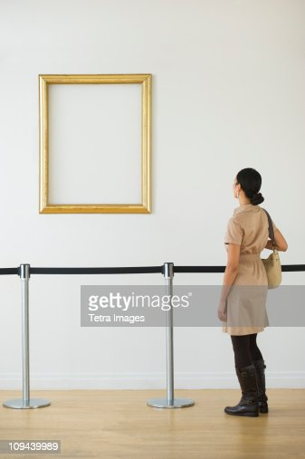 Woman looking at blank picture frame in art gallery
