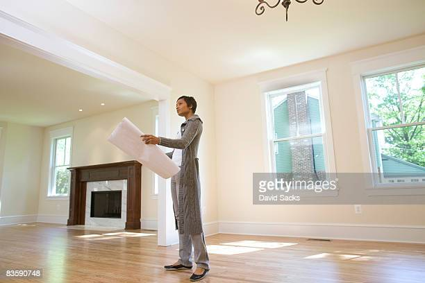 Woman looking at blueprints in newly built home