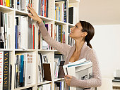 Woman looking at books on bookshelf, profile
