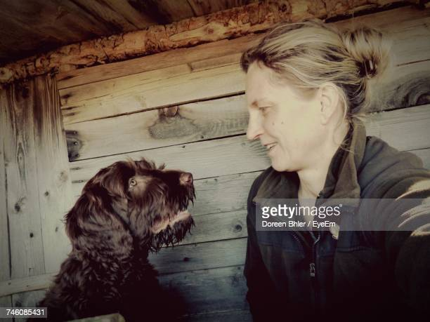 Woman Looking At Brown Dog Against Wooden Wall