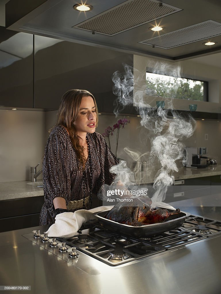 Woman looking at burnt turkey in kitchen