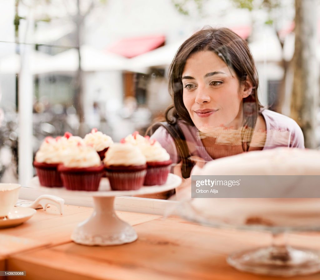 Woman looking at cake display in window : Stock Photo