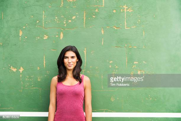 Woman looking at camera next to green wall