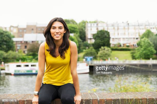 Woman looking at camera sat on wall