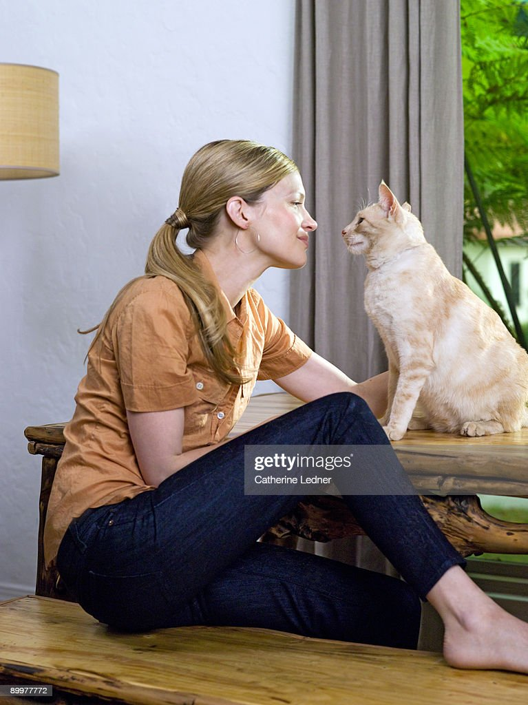 Woman looking at cat (Felis catus) lovingly : Stock Photo