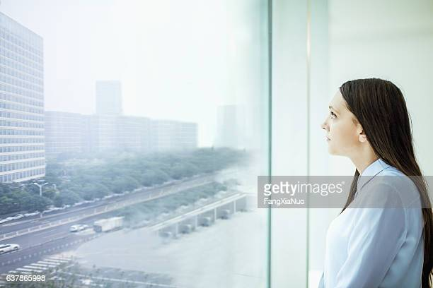 Woman looking at cityscape from window in office