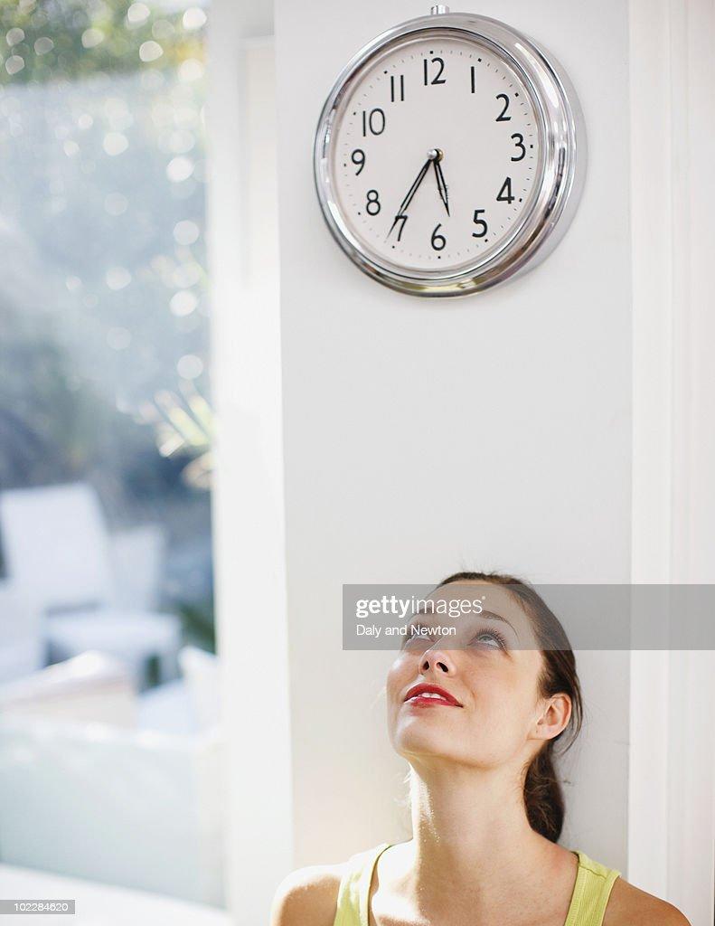Woman looking at clock : Stock Photo