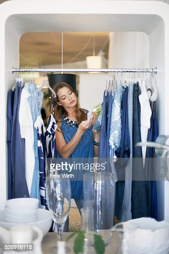 Woman looking at clothing on rack : Stock Photo