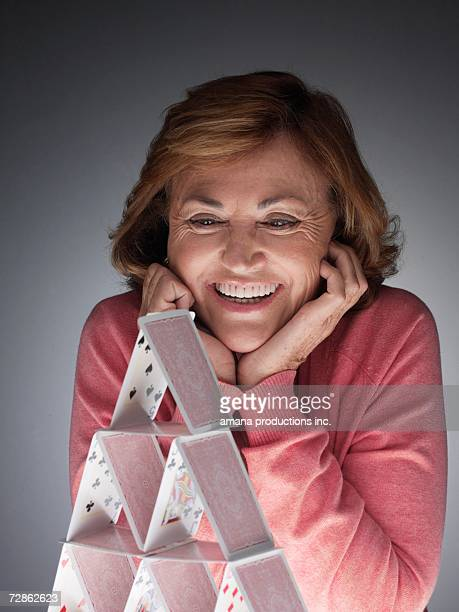 Woman looking at completed house of cards