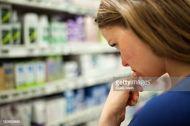 Woman looking at cosmetics in supermarket