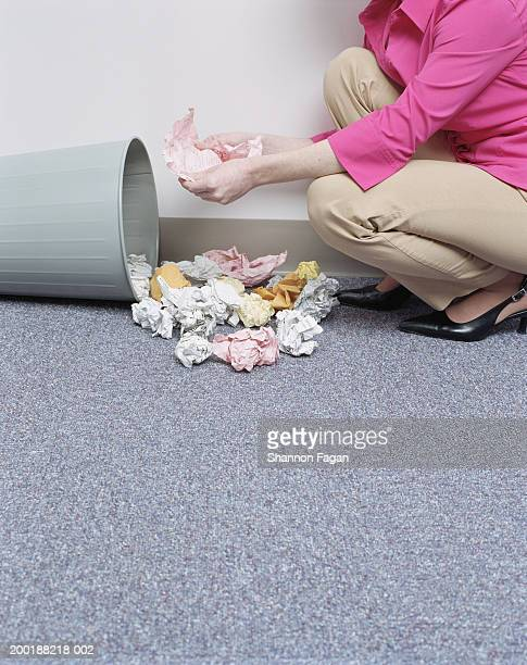 Woman looking at crumpled paper from trash can, mid section, side view