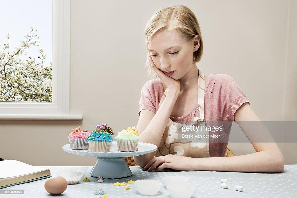 woman looking at cupcakes.