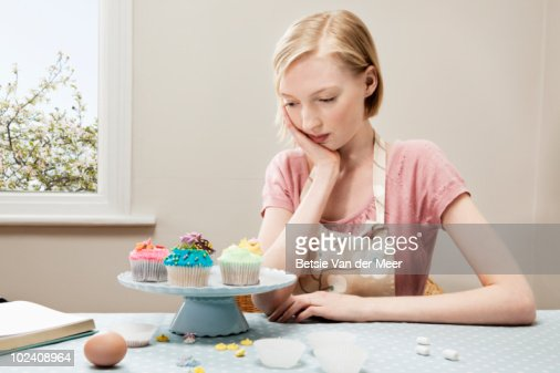 woman looking at cupcakes stock photo getty images - Woman Decorating Cupcakes