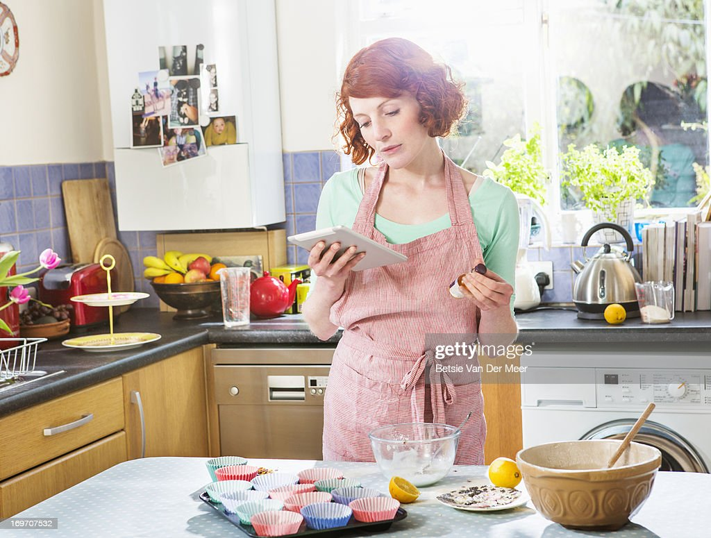 Woman looking at digital tablet for baking recipe.