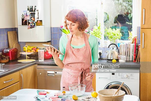Woman looking at digital tablet for baking recipe
