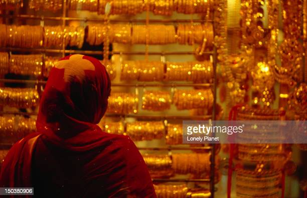 Woman looking at display of Dubai Gold suq.