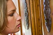 Woman looking at door keyhole