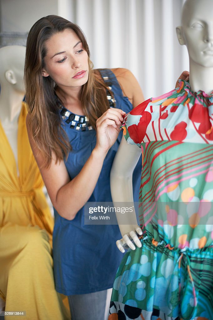 Woman looking at dress on mannequin : Bildbanksbilder