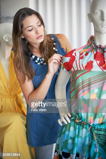 Woman looking at dress on mannequin : Stock Photo