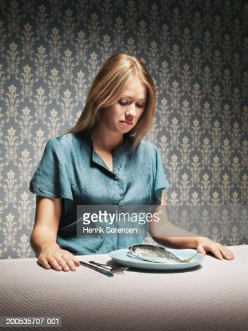 Woman looking at fish on plate at dinner table : Stock Photo