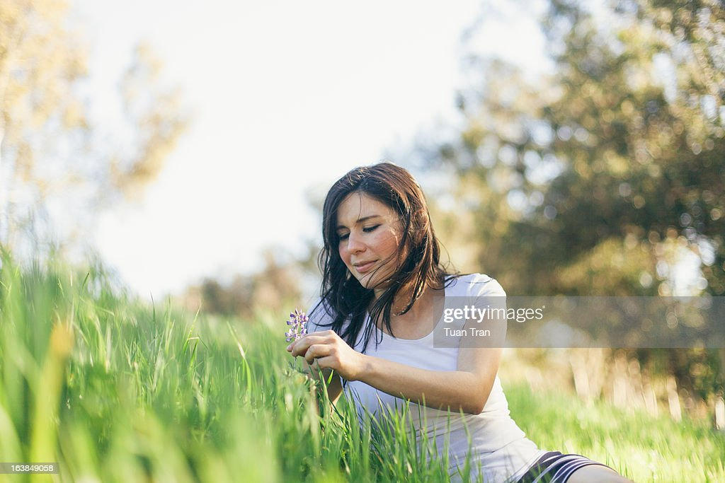 woman looking at flower : Stock Photo