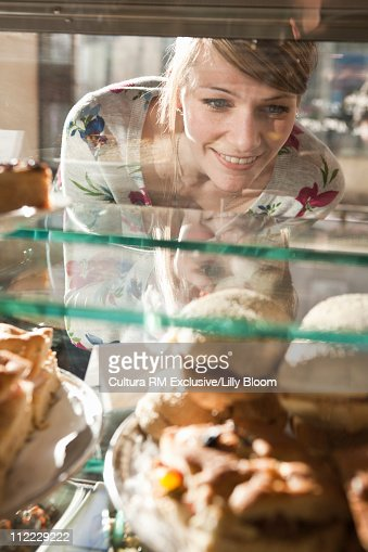 Woman looking at food in a glass case