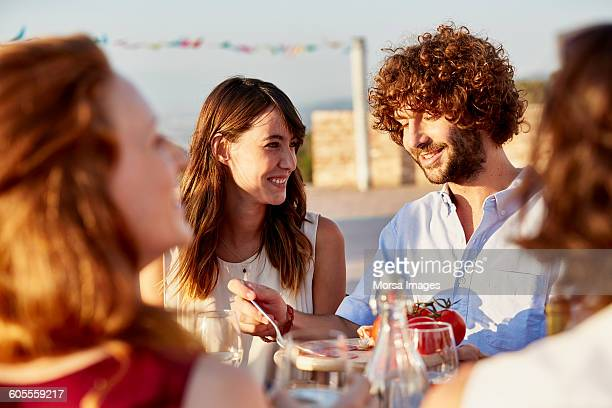 Woman looking at friend having food at gathering