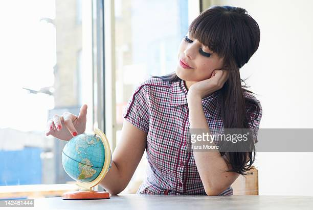 woman looking at globe of the world in cafe