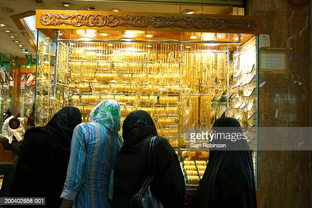 Woman looking at gold jewelry on display in shop, rear view