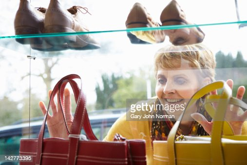 Woman looking at handbags in boutique window : Stock Photo