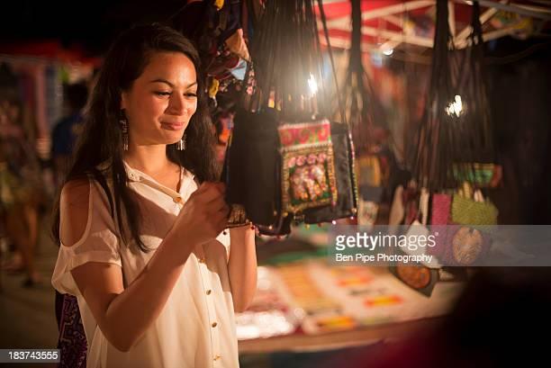 Woman looking at handbags in night market, Luang Prabang, Laos
